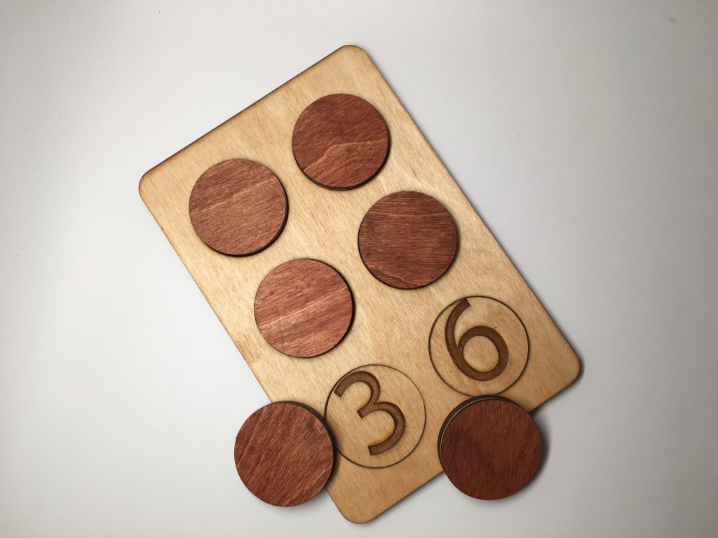 Braille Tactile Enlarged Learning Aid made out of wood. There are 6 circles aligned like a Braille cell that are set inside the outside container. When a circle is removed you can see the number that corresponds with the cell number.