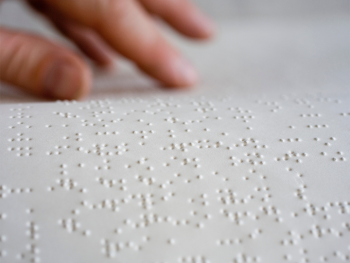 A close up view of Braille on thick paper with a persons hands touching the Braille to read it.